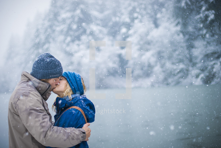 a couple kissing in the snow