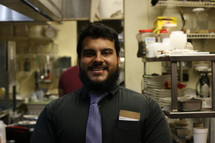 A smiling man standing in a restaurant kitchen.