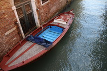 boat docked against a brick wall of a building in Venice