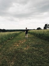 man walking through a freshly cut field of grass