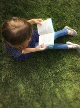 a child reading in grass