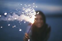 A woman holding a fiery sparkler.