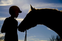 Silhouette of a boy with his horse.