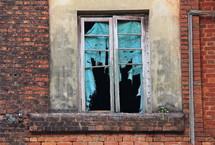 Tattered curtain in a broken window
