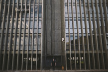man standing in front of a tall building