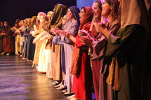performers dressed as shepherds singing on stage