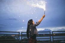a woman holding a sparkler
