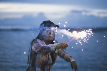 woman holding a sparkler under a cloudy sky