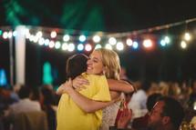 friends hugging at a wedding reception