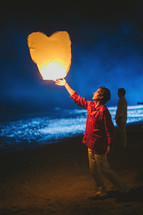 man releasing a heart shaped paper lantern
