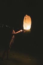 woman releasing a paper lantern
