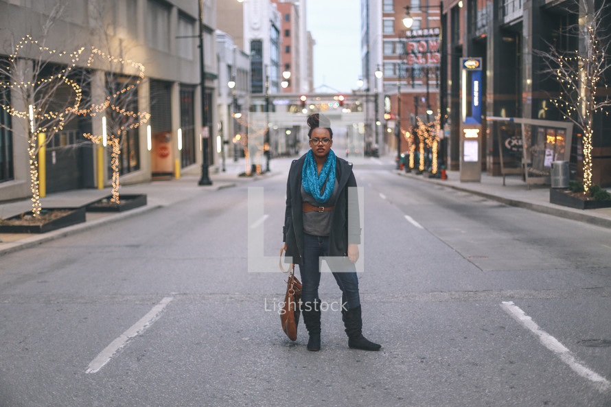 woman standing in the middle of a street dragging her purse