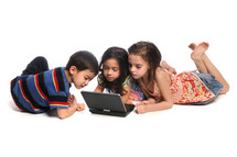 Three children on the floor looking at a laptop computer.
