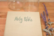 Holy Bible, lavender, and glass bottles on wood