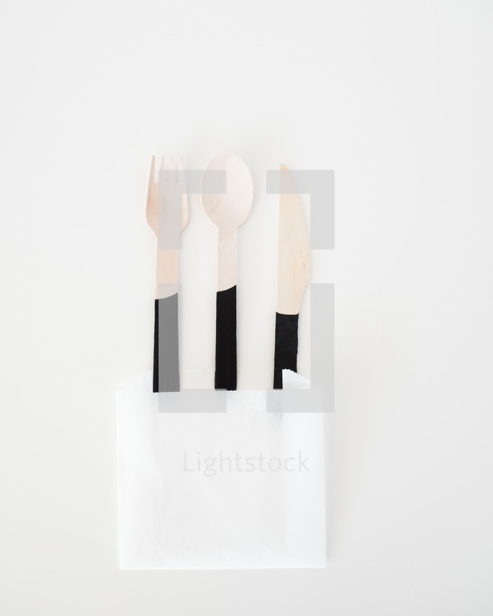 wooden fork, spoon, and knife in a napkin