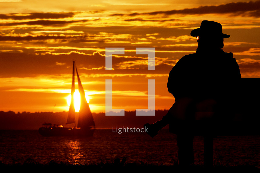 man watches sailboat at sunset