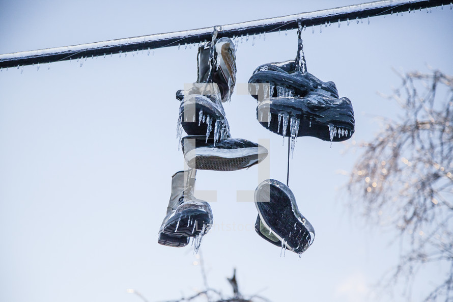 Frozen Shoes on a line are covered in ice from an ice storm