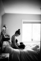pregnant mother sitting on a bed