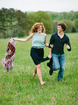 man and a woman running barefoot in a grass field