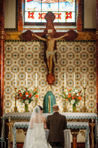 crucifix above a kneeling bride and groom