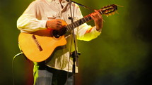 Guitarist playing his spanish classic guitar at live music concert