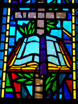 A colorful stained glass window depicting the Cross and the word of God in vivid blue, gold, green and red colors adorning a church sanctuary.