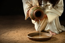 Kneeling Jesus pouring water from an urn into a bowl.