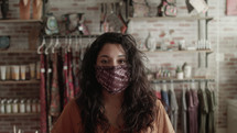 a woman in a boutique wearing a face mask