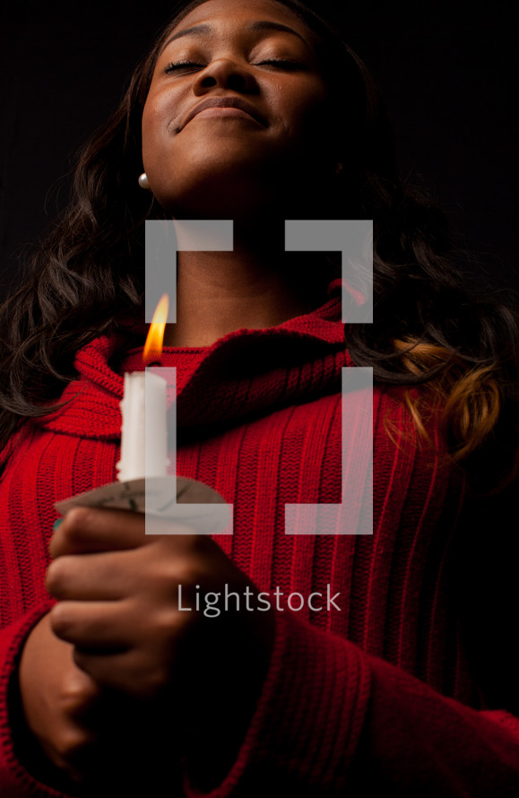 A woman holding a candle at a Christmas Eve service.