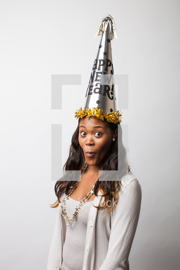 A woman wearing a Happy new Years party hat.
