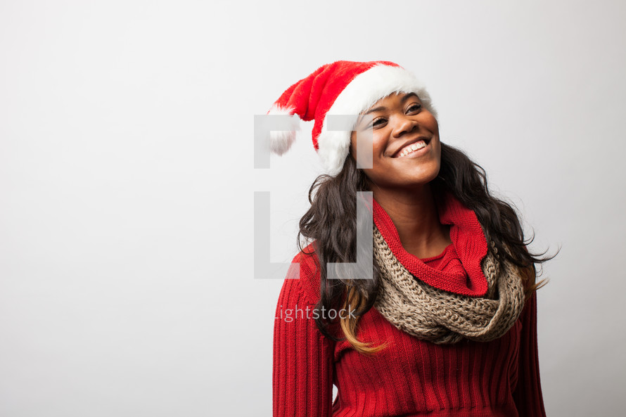 A woman in a Santa hat looking up to God.