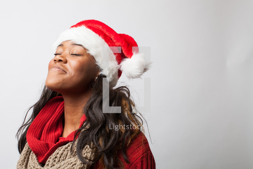 A woman wearing a Santa hat looking up.