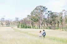 Couple walking in a grassy field near a tree line.