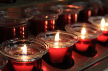 Rows of beautiful red Candles reflect the holidays and light up a church during a prayer vigil or Christmas Eve Service in a church during the Christmas season.