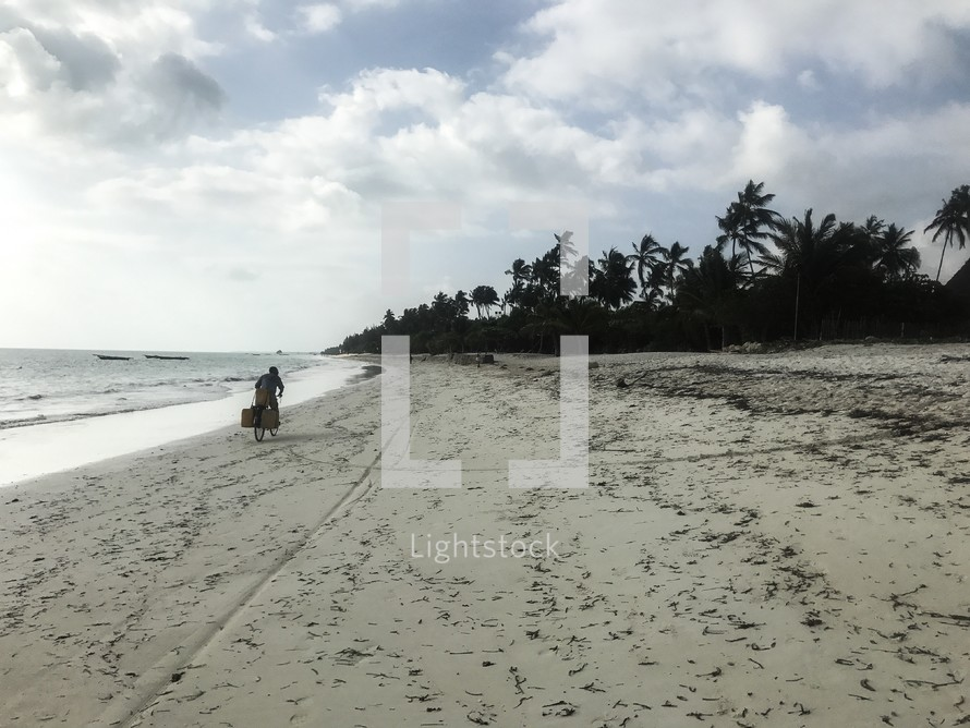 a man riding a bike on a beach in Zanzibar, Tanzania