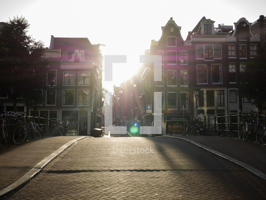 sunburst between buildings in Amsterdam, Netherlands