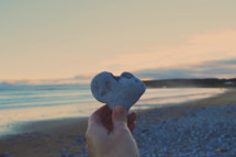 a hand holding up a heart shaped rock