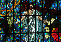 The story of Jesus told visually in a stained glass window showing Jesus resurrected with the cross, 30 pieces of silver that Judas used to betray Jesus, and the rooster that crowed before Peter denied Jesus publicly.