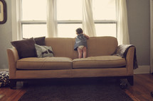 Toddler child standing on a sofa looking out the window.