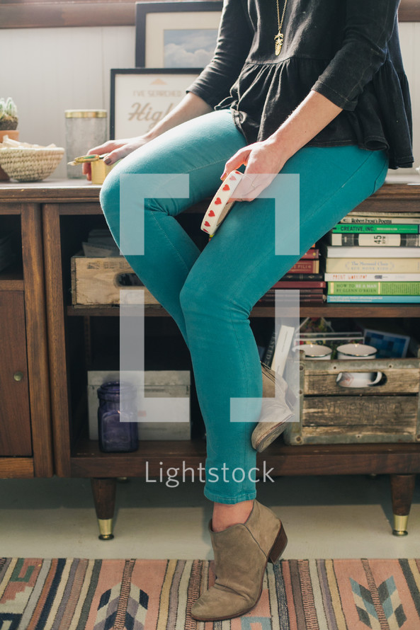 a woman sitting on a bookshelf holding tape and scissors
