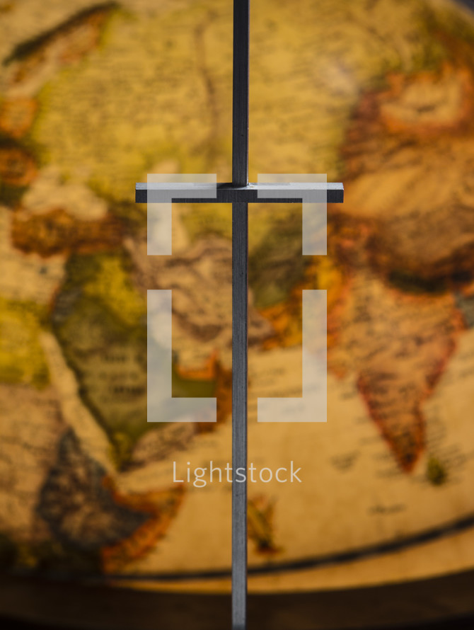 cross in front of a globe