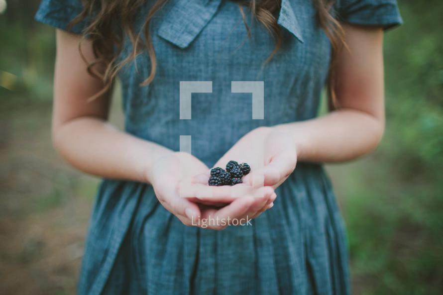 girl with hand full of blackberries