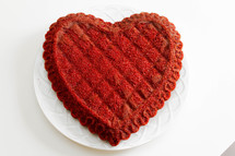A red heart shaped cake.