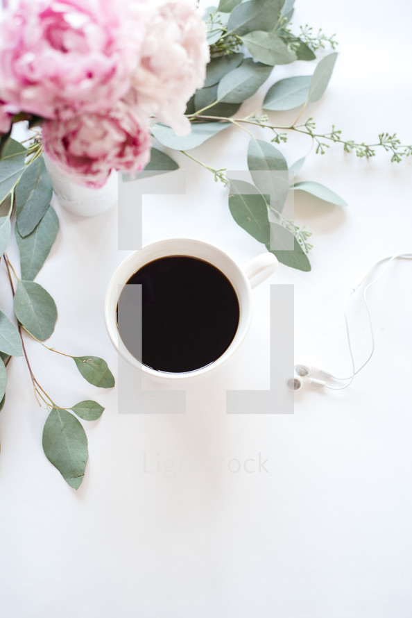 A cup of coffee and a bouquet of flowers on a white surface.