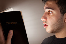 man reading the Bible in amazement