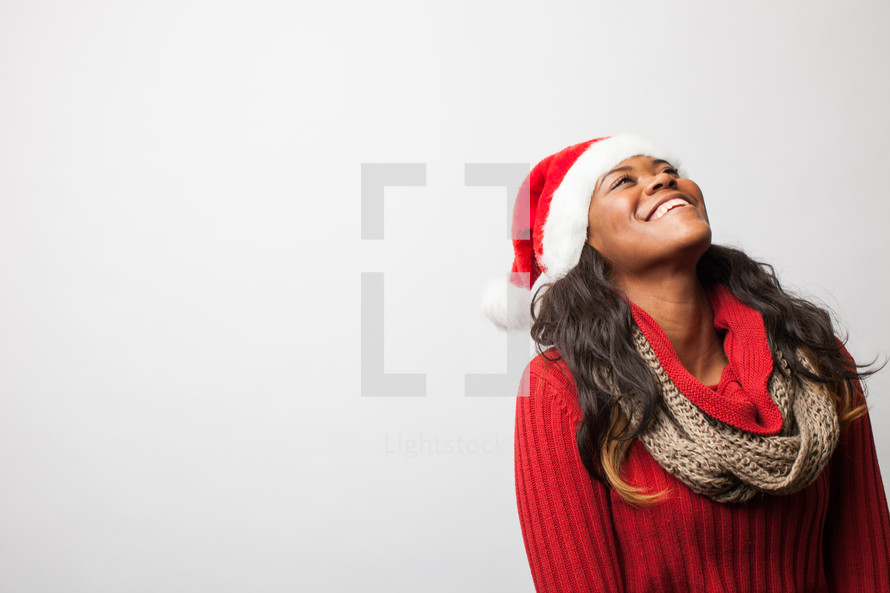 A woman in a santa hat looking up.