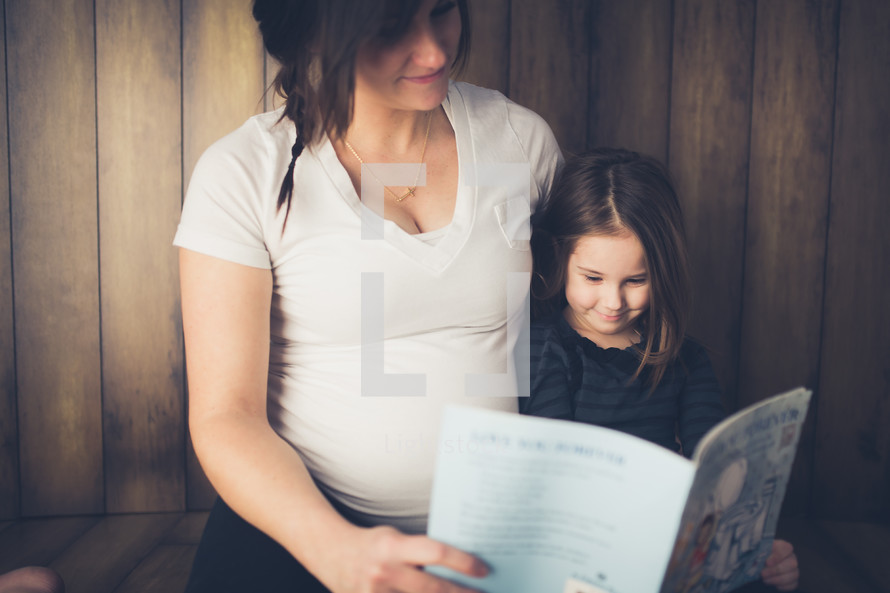Expecting mother sitting on the floor reading a book with her daughter.