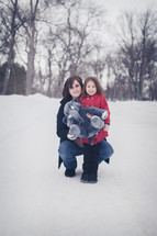 mother and daughter in the snow holding a stuffed animal elephant