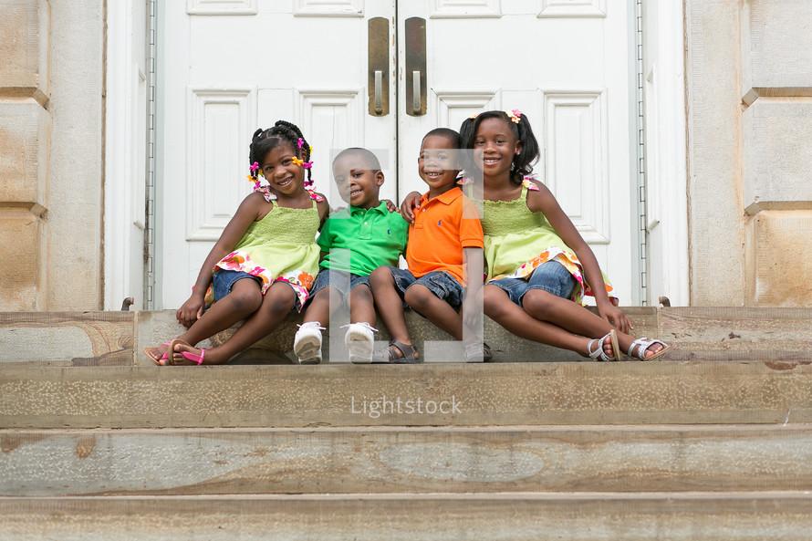 Happy siblings sitting on church steps