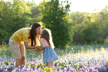 Mother and young daughter kissing in field of purple wildflowers